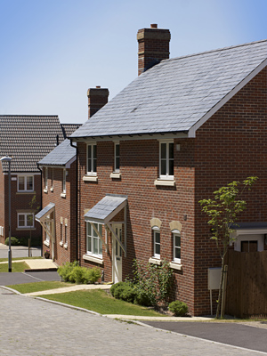 stock-photo-a-new-modern-housing-development-a-row-of-recently-built-new-houses-constructed-of-red-brick-with-55733704